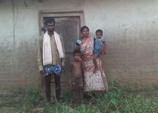 Samari Kasabi's son, Sukura (left), and his family outside their village home in Dokawaya, Chhattisgarh.