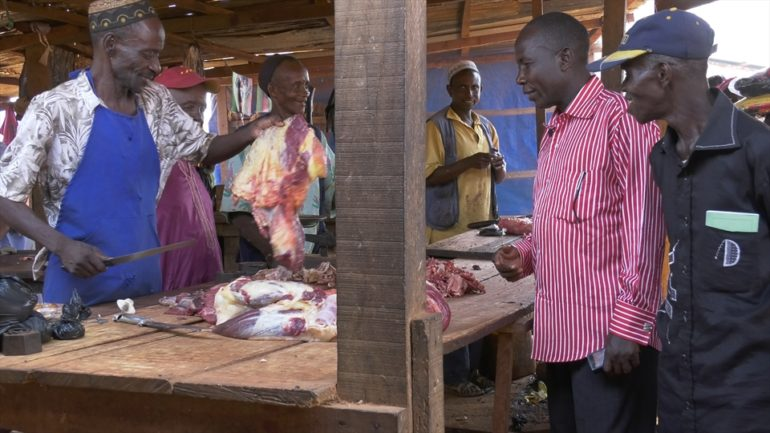 Pastors Jean and Pierre buy meet from a Muslim butcher in the market. (Photo: World Watch Monitor)