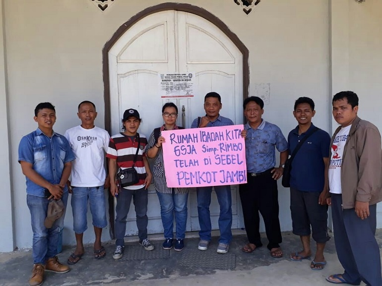 "Members of one of the closed churches hold a sign that says: ""Our church Assemblies of God has been sealed by the government"". (Photo: World Watch Monitor)"